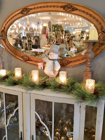 lighted candle strand and snowman in front of gold vintage mirror