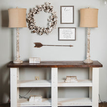 console table with buffet lamps and cotton wreath on wall