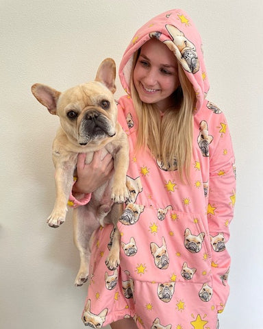 Women holding french bulldog wearing oversized pink hoodie with custom dog photos on it