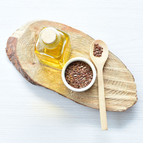 Flax seeds sitting on wood riser with oil