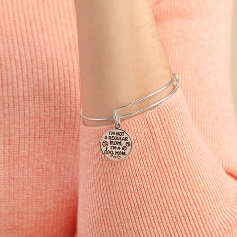 •	Alex and Ani charm bracelet on women's arm with pink sweater.
