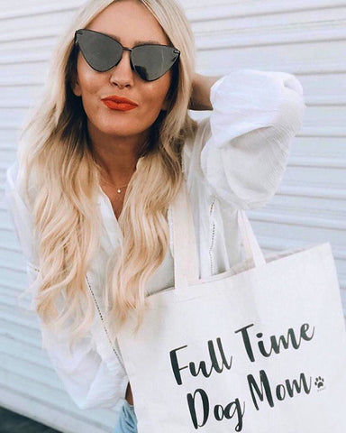 •	Women wearing sunglasses and carrying white 'dog mom' tote bag