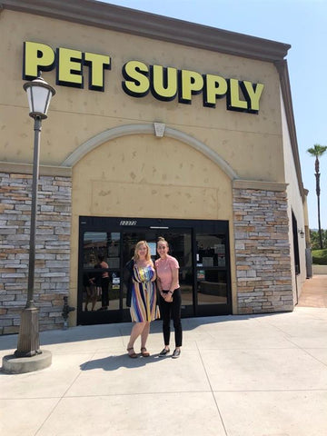 Marketing team stands outside of Pet Supply entrance