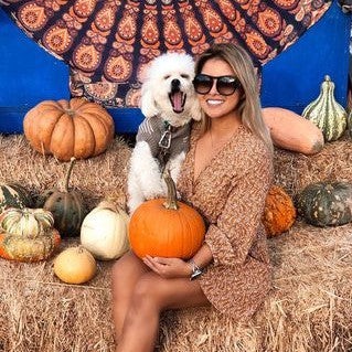 Woman and dog sitting on hay at pumpkin patch