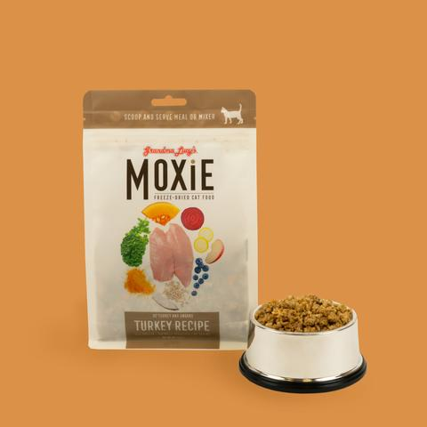 Brown background with bag of Moxie food with bowl of Moxie