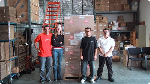 Owners Eric and Breann with their first two employees standing in front of the first pallet shipment