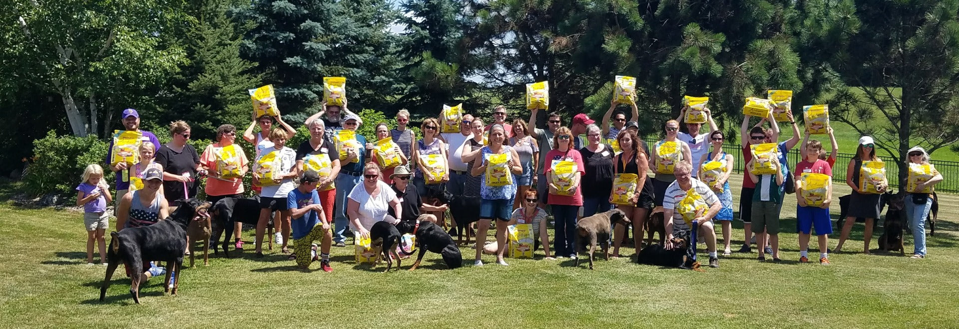Organization with all members holding bags of Artisan Chicken dog food