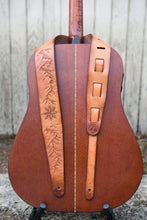 Leather guitar strap with hand tooled topographic mountains and compass rose shown on guitar