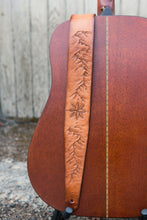 Details of hand tooled topographic mountains and compass rose on leather guitar strap