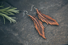 Leather earrings hand-carved, dyed and cut to look like feathers.