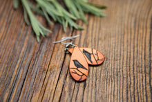 Leather teardrop shaped earrings with a hand-tooled design featuring a bird resting on a branch.
