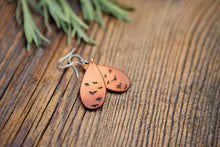 Leather teardrop earrings with hand-tooled design of birds in flight