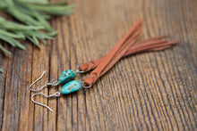 Turquoise & Leather Fringe Earrings lying on wooden background.