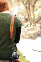 Woman wearing hand carved feather camera strap over her shoulder