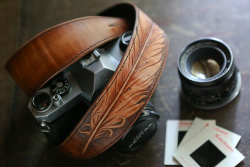 Hand carved feather on leather camera strap with camera, lens and film slides