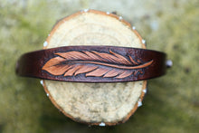 Detail of hand carved feather on leather cuff bracelet