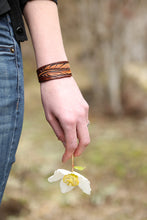 Model holding a flower wears the leather Feather Cuff Bracelet