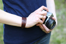 Model holding a camera wears the leather Engraver's Scroll Cuff Bracelet