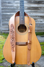 Leather guitar strap with intricate hand carved scrollwork shown on guitar