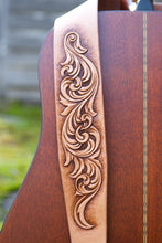Detail of hand carved and hand tooled leather scrollwork on guitar strap