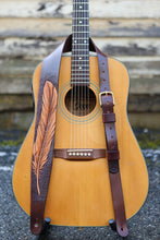 Hand carved feather guitar strap shown on guitar