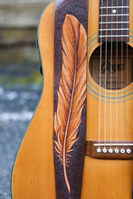 Details of hand carved and tooled feather on leather guitar strap