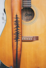 Details of hand carved and tooled lodgepole pine tree on leather guitar strap