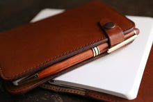Leather journal with strap closure provides a place for a favorite pen