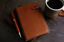 Handcrafted leather journal on desk with pen and cup of coffee
