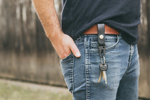 Man wearing black leather HK clip key fob on his belt