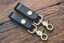 "Black leather key fobs with solid brass trigger snap, shown in two widths: 3/4"" and 1"""