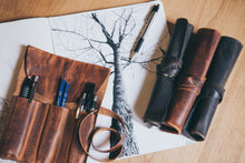 Three rolled up tool rolls with one open tool roll containing pens and pencils sit on sketch of a tree