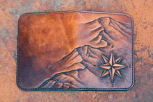 Flat-lay of handcrafted leather wallet with Cascadia mountain design hand-tooled on the front