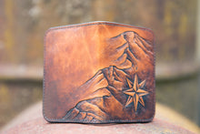 Handcrafted leather wallet with tooled design featuring a topographical mountain range and compass rose