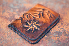 Front detail of hand-tooled wallet showing compass rose, mountain range and polished wallet edges