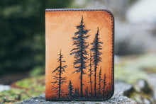 Handcrafted leather wallet with tooled design featuring a forest of lodgepole pine trees