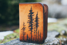 Front detail of hand-tooled wallet showing lodgepole pine trees