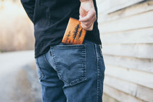 Man placing handcrafted lodgepole pine tree leather wallet into the back pocket of his jeans