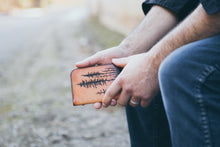 Man holding handcrafted leather wallet with tooled lodgepole pine forest design on front
