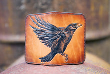 Handcrafted leather wallet with tooled design featuring a large raven across the front of the wallet