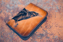 Front detail of hand-tooled wallet showing raven head and polished wallet edges