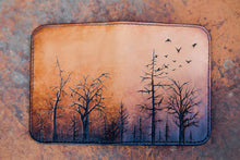 Flat-lay of handcrafted leather wallet with silent forest design hand-tooled on the front