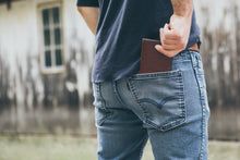 Man putting Four Pocket leather wallet into the back pocket of his jeans