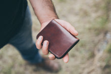 Man holding folded four pocket leather wallet in rich brown