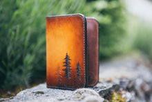 Front detail of hand-tooled wallet showing small lodgepole pine trees