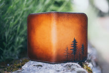 Front and back detail of hand-tooled wallet showing small lodgepole pine trees