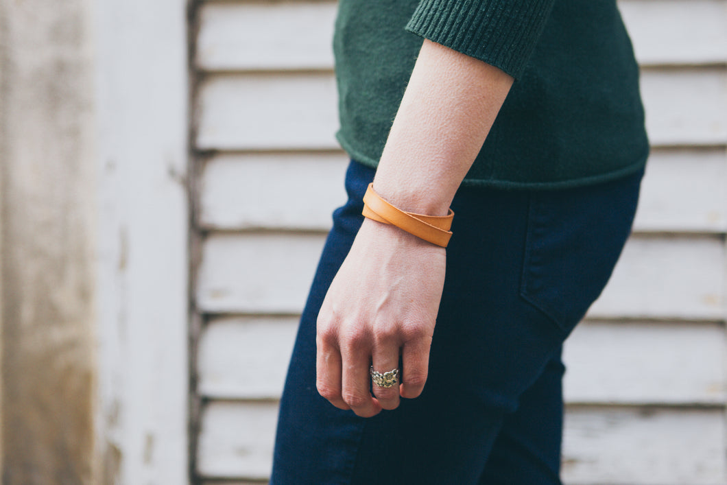 Woman wearing solid leather wrap bracelet in Natural.