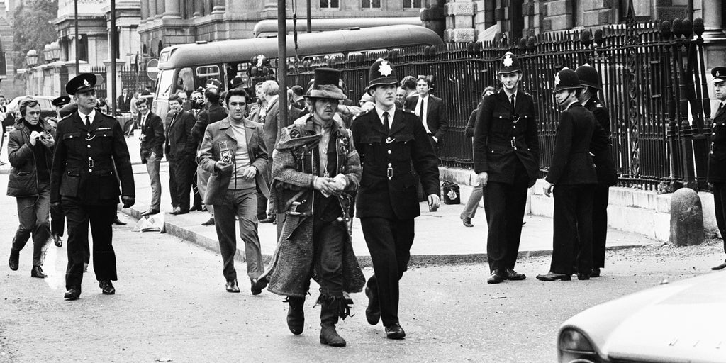 A top-hatted hippie is led away from 144 Piccadilly by a policeman on 22nd September 1969