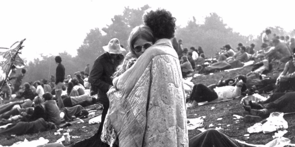 Hippie couple empbrace on a hill at the Woodstock Music & Art Festival held in Bethel, NY in 1969