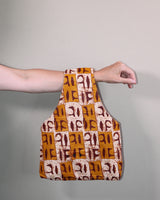 Carry one of our medium knitting bags over your arm when you're knitting on the go. Handmade in Africa with a pretty, brown waxed cotton print by Chameleon Goods.